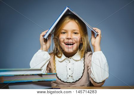 school concept. happy girl sitting at desk and holding book on her head.