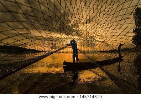 Asian fisherman on wooden boat casting a net for catching freshwater fish in nature river in the early morning before sunrise