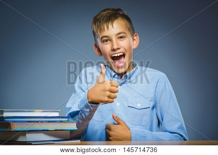 school concept. Smiling happy boy sitting at desk and show thumbs up.