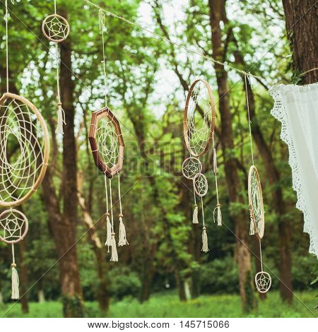 Decor with dream-catchers on a green forest background