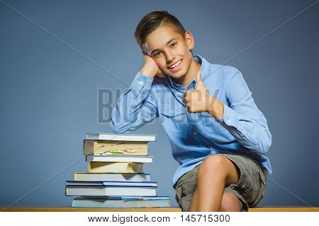 school concept. Smiling happy boy sitting on desk and show thumbs up.