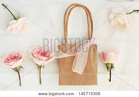 Tender delicate pink and white rose buds in craft paper shopping bag. Creamy toned present.