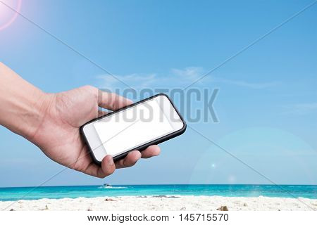 Hand holding Smartphone over beach and blue sky background