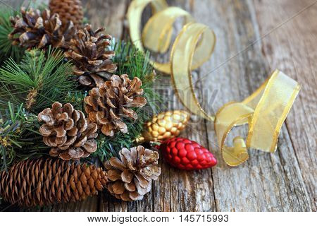 Background: pine cones and New-Year tree decorations on a wooden background