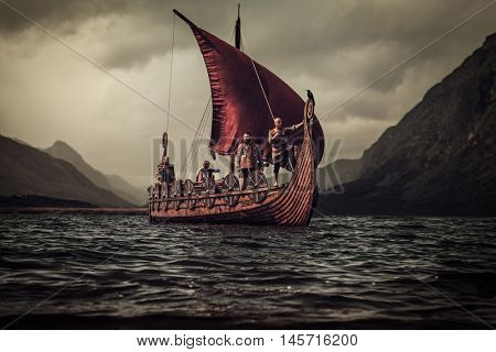 Group of vikings are floating on the sea on Drakkar with mountains on the background.
