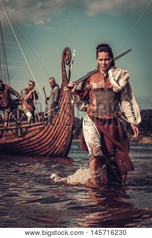 Confident viking woman with sword walking along the shore with Drakkar on the background.