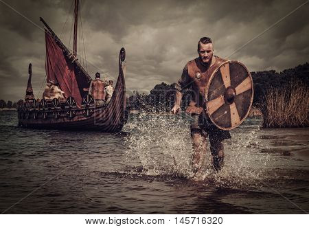 Serious viking warrior in the attack, running along the shore with Drakkar on the background.