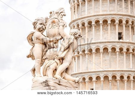 Close-up view on Putti fountain with Pisa leaning tower in Italy