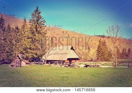 Spring mountain landscape in vintage style. Wooden hut in Koscieliska Valley in Tatra Mountains Poland.