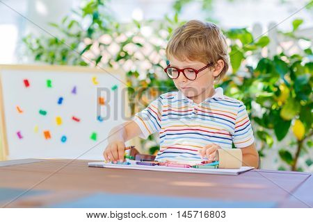 Funny adorable little kid boy with glasses holding wax crayons pens. Happy child and student is back to school and looking at pupil's stuff on warm day.