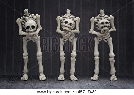Three skeletons holding their own head with black background