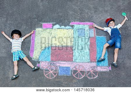 Two little kids boys having fun with train or steam locomotive picture drawing with colorful chalks on ground. Children, lifestyle, fun concept. funny friends playing and dreaming of future and profession.