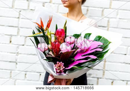woman with bouquet of pink peonies in kraft paper on background of a brick wall