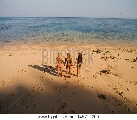 Female Friends Standing On The Beach Holding Hands