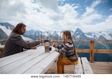 Father with daughter drinking warm tea in the rustic wooden outdoor cafe on mountain, alpine view, snow on hills. Winter weekend. Dombay, Karachay-Cherkessia, Caucasus, Russia.