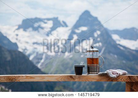 Tea on terrace on the mountain, alpine view, snow on hills. Dombay, Karachay-Cherkessia, Caucasus, Russia.