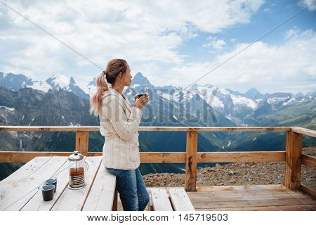 Woman drinking warm tea in the rustic wooden outdoor cafe on mountain, alpine view, snow on hills. Dombay, Karachay-Cherkessia, Caucasus, Russia.