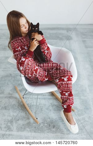 10 years old child dressed in warm Christmas pajamas sitting with black kitten on modern rocking chair in concrete scandinavian interior. Lazy winter morning, comfortable scene.