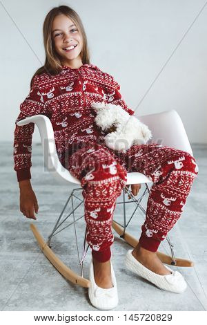 10 years old child dressed in warm Christmas pajamas sitting on modern rocking chair in concrete scandinavian interior. Lazy winter morning, comfortable scene.