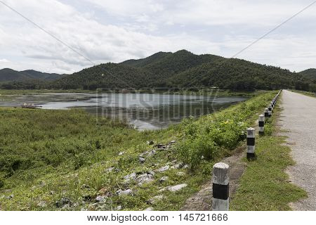 Road Beside Mountain Hill And Pond