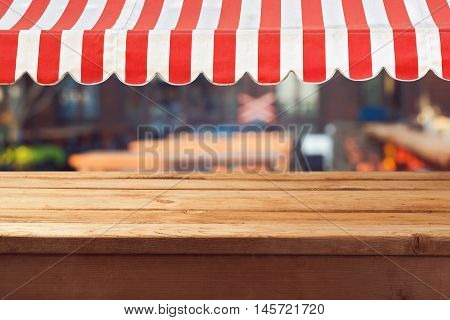 Empty wooden deck table with awing for product montage display