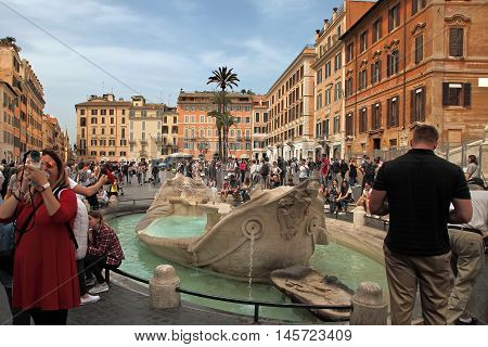 ROME ITALY - APRIL 7 2016: Piazza di Spagna - popular meeting places in Rome. Fontana della Barcaccia - elegant looking fountain commissioned by pope Urban VIII designed by Gian Lorenzo Bernini.