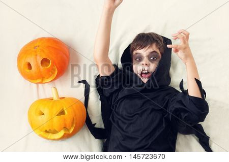 Child in scary costume with pumpkin. Child in halloween outfit on white background