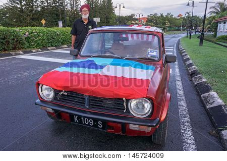 Kota Kinabalu,Sabah-Aug 31,2016:Portrait of man in antique car with Sabah flag during National day parade,celebrating the 59th anniversary of independence on 31st Aug 2016 at Kota Kinabalu,Sabah