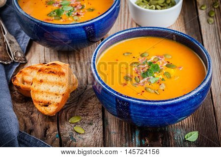 Homemade Autumn Butternut Squash Soup With Pumpkin Seeds, Bacon And Basil