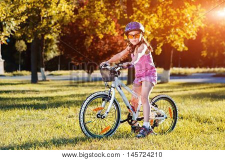 The child riding a bicycle. The kid in a helmet riding a bike in the park. Beautiful baby.