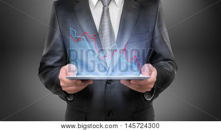 Cropped portrait of a businessman holding tablet with falling diagram above it. Economic and financial crisis. Business recession. Decline and setback.