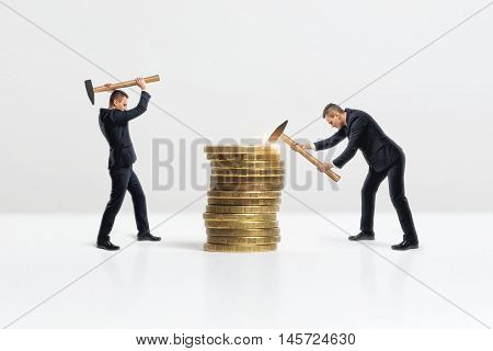 Side view of a businessmen crashing big stack of golden coins with hammer, isolated on white background. Making money. Business staff.