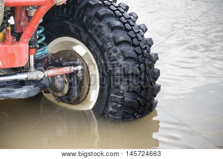 Details of 4x4 off-road car tyre on water river.