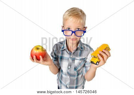 Wide angle close-up portrait of boy a student in shirt in glasses hugging apple and schoolbus in hands looking at camera isolated on white background. School preschool