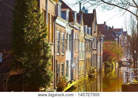 Delft street view with traditional dutch houses, bicycles, canal in downtown of popular Holland destination