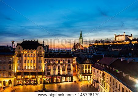 Aerial view of Bratislava Slovakia at night. Famous castle and illuminated historical buildings with bars cafes restaurants and shops