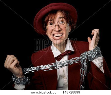 Strange person in a suit and bowler trying to free herself from the chain on her hands.