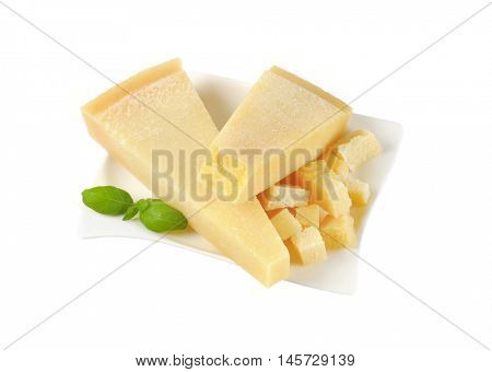 wedges and pieces of parmesan cheese on white plate