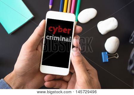 Cyber criminal, text message on screen at hands take smartphone, black table with office supplies backdrop background . business concept.