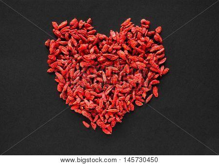 Raw dried goji berries arranged in a heart shape on a black background