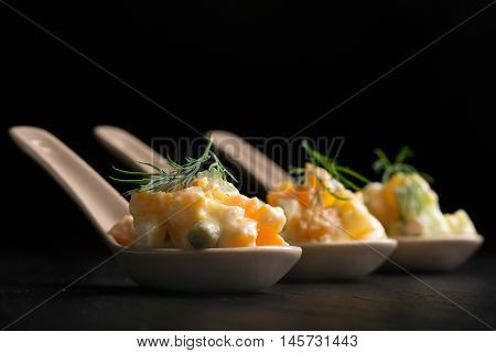 Traditional Russian salad olivie with boiled vegetables and mayonnaise on a black background. Portion Control spoon