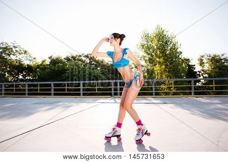 Side view of a beautiful young roller girl in blue swimsuit posing outdoors on the open road
