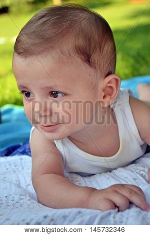 Happy baby boy crawling portrait in outdoor park.
