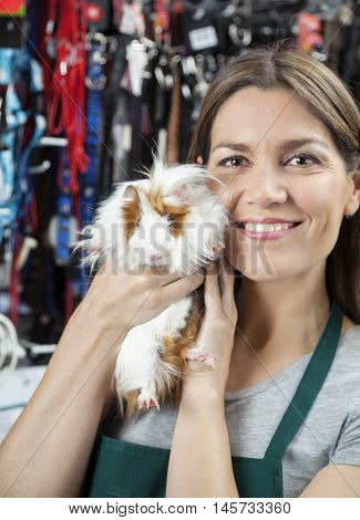 Happy Saleswoman Holding Cute Guinea Pig At Store