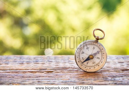 Vintage compass on grunge wooden table and bokeh nature background
