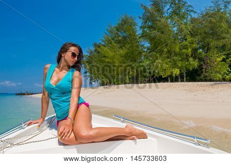A stunningly beautiful young woman on a speedboat at the tropical beach