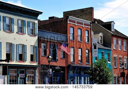 Baltimore Maryland - July 22 2013: 18th and 19th century brick buildings line the Thames Street waterfront and house trendy shops pubs and restaurants at historic Fells Point