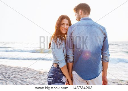 Beautiful young woman holding her boyfriend hand who standing backwards at the beach