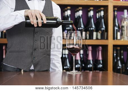 Midsection Of Bartender Pouring Red Wine In Glass