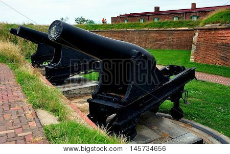 Baltimore Maryland - July 24 2013: Cast iron cannons on swivel wheels aimed at Chesapeake Bay on the defensive outer walls at Fort McHenry National Historic Park